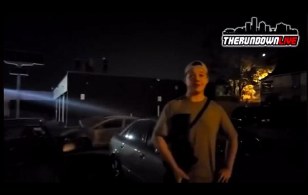 Kyle Rittenhouse (v popředí) a dotčený obchod s auty, na jehož střeše stojí 3 další ozbrojení civilisté.