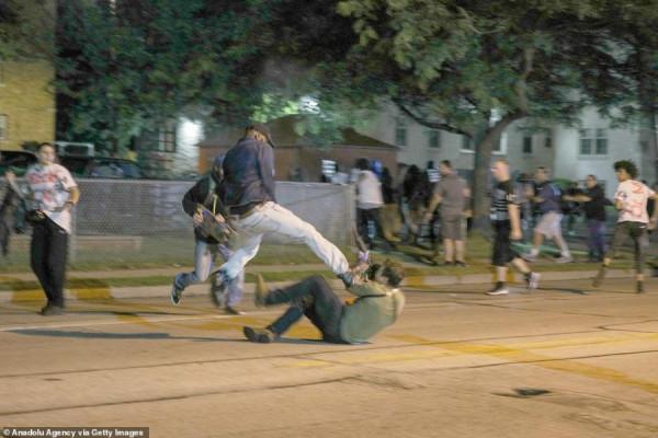 Neznámý útočník, kopající do Kyla a Anthony Huber, připravující se k útoku.
