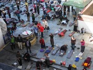 Buddhističtí věřící, připomínající muslimy, se modlí před tibetským klášterem...