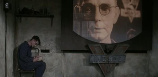 Winston si píše do svého deníku mimo zorné pole televizní obrazovky, která funguje zároveň i jako kamera. Psací potřeby jsou totiž zakázány.