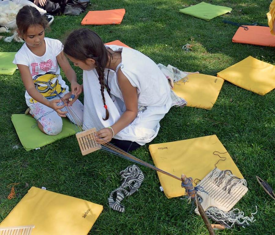 Děvčata zaujatá tvorbou ozdobných pásků tkaných na destičce.