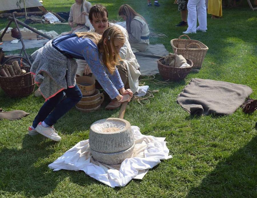 Ruční mletí zrna kamenným mlýnkem je namáhavé.