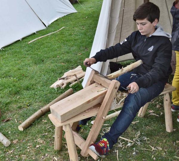 Chlapec sedí na truhlářské stolici, zvané též kozlík; pracovním nástrojem je poříz.