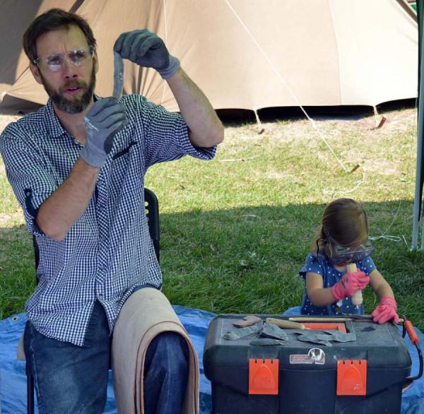 Štípání pazourku s ukázkou čepelové techniky předvádí profesionál pan Zítka a vedle se činí jeho tříletá dcerka.