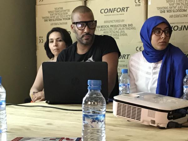 Zaměstnanci neziskové organizace v Marakeši bojující s HIV nám vysvětlují princip své práce. Za nimi jsou bedny s kondomy.