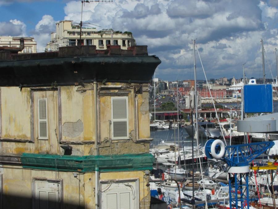 Rozpadající se obytný dům a jachty v pozadí. Pohled z hradu Castel dell'Ovo směrem na východ. Chudoba a bohatství tu stojí přímo vedle sebe.