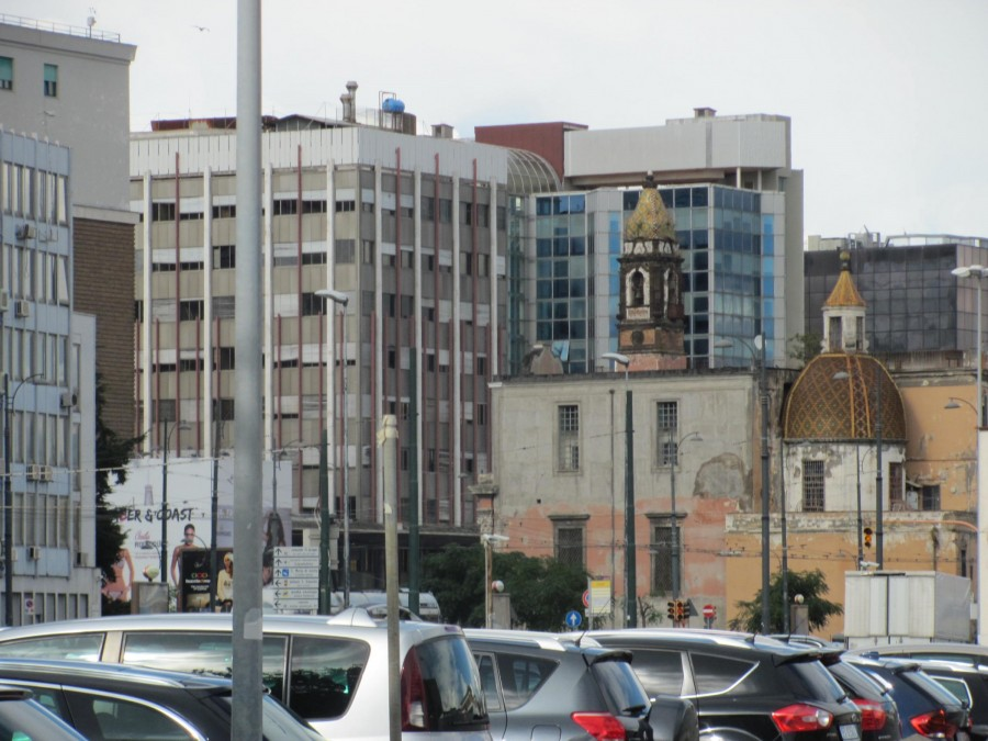 Malá ukázka svérázné zástavby. Pohled od moře, v pozadí začíná  Il Centro Direzionale di Napoli, moderní část města dostavěná v roce 1995 dle plánů japonského architekta Kezo Tange. Mrakodrapy byly vystavěny v přímém sousedství čtvrti Poggioreale, známé hlavně díky největšímu vězení v jižní Itálii. Čtvrť Poggioreale nese do dneška stopy bombardování z dob druhé světové války. Kontrast mezi sousedícími čtvrtěmi je podobný jako kontrast mrakodrapů v pozadí a budovy v popředí fotografie.