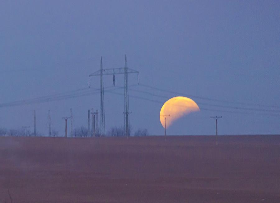 Měsíc zapadající za obzor, ještě stále zastíněný ve spodní části. 21. ledna 2019, 07.19 hod.